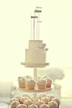 Simple two-tiered white cake with matching polka dot cupcakes. Cute alternative to a big cake.