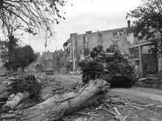 Boulevard Alsace-Lorraine à Coutances,  29 juillet 1944. Trois chars légers américains M5A1 Stuart du 25th Cavalry Recon Squadron (Mechanized) de la 4th Armored Div. encadrants une jeep.