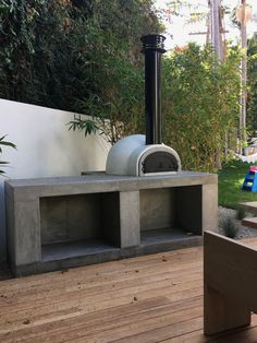 Modern wood patio with concrete outdoor kitchen. Design includes pizza oven with storage below. Modern Outdoor Pizza Ovens, Outdoor Barbeque, Outdoor Kitchen Patio, Pizza Oven Outdoor, Outdoor Kitchen Design, Outdoor Fire, Outdoor Cooking, Wood Patio, Rooftop Design