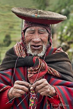 Elderly man of the village of Chinchero knitting at the Sunday market in the Sacred Valley of Peru.