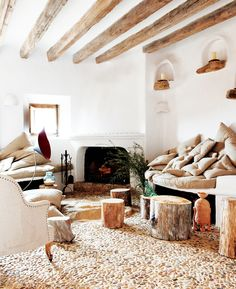 White plastered walls with exposed ceiling beams and stone floors, stumps for coffee tables, and lots of neutral furniture and pillows