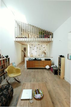 this wooden partition is a great way to connect both spaces and allowing for the room to be opened up