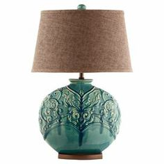 "Round turquoise lamp with a raised vine pattern.    Product: Table lamp    Construction Material: Ceramic and fabric      Color: Turquoise and chocolate     Features: Raised vine and leaf pattern        Accommodates: (1) 150 Watt bulb - not included  Dimensions: 28"" H x 16"" Diameter"