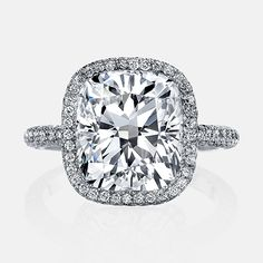 ATHENA is a custom engagement ring set with a stunning 5 carats Cushion cut diamond inside a Micro Seamless Halo™ and tapered straight stems.