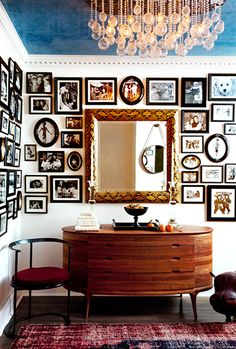framed black and white photos, snakeskin frame mirror, crystal drop chandelier, and walnut console table // foyers