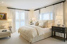 .bed in front of window w/ curtains framing