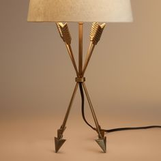 A unique balancing act, our exclusive antique brass finish table lamp stands on the points of four intricate feathered arrows. This modern and minimalist statement piece is perfect for any room.