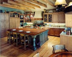While remaining inviting and warm, this galley kitchen is an evocative of a commercial kitchen. The expansive rustic kitchen island idea is highlighted by the pale blue base and rustic seating for three at the bar