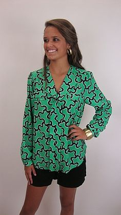 Lilly Pulitzer meets Tory Burch in this new blouse! It is kelly green with a black and white print, making it an easy match with any black bottom. Wear it casually with black shorts and pointy toe flats or wear it to work with a black pencil skirt and pumps! This is a pull-over style with button cuffs. | I MUST have this! On point with my style! #shopbluedoor