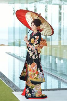 A traditional Japanese kimono with bright, cheerful details and an orange and white parasol, so beautiful!