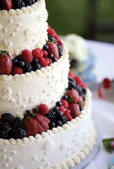Brides.com: . The buttercream-frosted wedding cake, by Cakes by Charlie, was decorated with fresh berries.