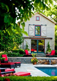 White washed barn with pops of bright colors and beautiful rock and brick materials to complement the greenery..