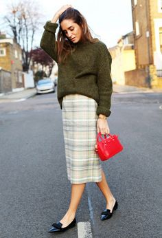 A hunter green sweater is paired with a plaid knee-length skirt and black pointed-toe flats.