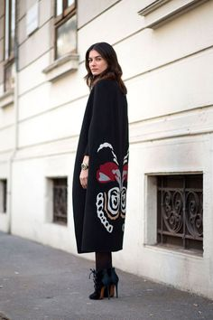 Leila Yavari in a black cape + black tights + lace-up ankle boots