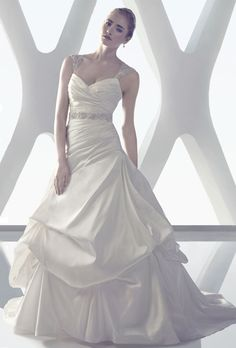 Amar� Couture Bridal. More Details From CB Couture��Silk shantung gown with an asymmetrical ruched bodice flows into a billowy pick-up skirt. Swarovski crystals, rhinestones, and pearl beads adorn the sheer beaded cap sleeves and beaded keyhole back neckline. This fit-and-flare gown includes a detachable beaded silk shantung sash and has matching fabric covered buttons and loops along the zipper.