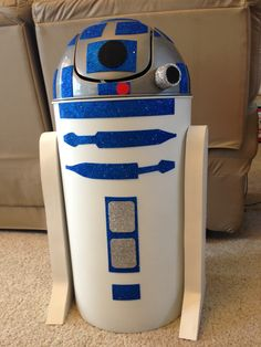 R2D2 You can't find a white round garbage can w/ dome shaped lid, buy a silver one & spray paint the bottom white. ($12 at big lots). Use glitter foam sheets w/ the sticky back for all details. By 2 large sheets of 1/2 inch foam board ($6 each at Michael's) to make the thick legs & hot glue a strip of poster board @ the legs so you don't see the 3 boards glued together. Attach the legs to the can w/ hot glue. TP roll lined with the glitter foam paper for the camera piece. KIDS LOVE IT!