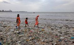A Family Walks On A Garbage-strewn Beach In Mumbai