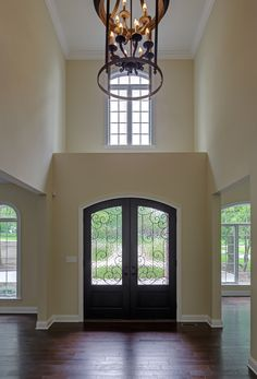 DH Custom Homes, custom Pendleton in Chesterfield, MO. As you enter the home, you are welcomed by a beautiful pair of arched, stained mahogany doors with iron glass inserts. That's what we call a warm, and beautiful, welcome! #entry #frontdoor #door #foyer