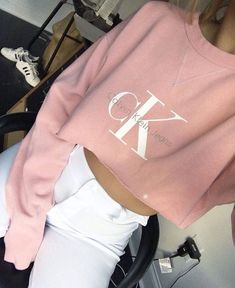cK baby pink crop shirt with white high-waisted jeans .