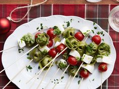 Tortellini Skewers -4 tablespoons olive oil 2 tablespoons jarred pesto 2 teaspoons red wine vinegar 2 packages spinach tortellini, cooked and cooled 2 pints cherry tomatoes 12 ounces fresh mozzarella, cubed 1/4 cup minced fresh parsley