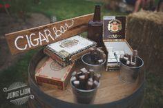 Wedding reception cigar bar. Vintage cigar boxes. Repurposed wood sign. Galvanized buckets. Wine barrel. Barn wedding. Rustic wedding.
