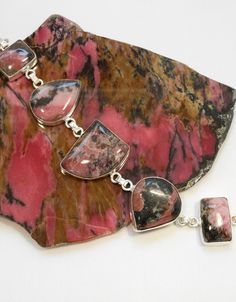 "Handmade artisan Australian Rhodonite bracelet with 5 polished cabachon gemstones, bezel-set in 925-hallmarked sterling silver with sterling links. Length 7-9"" Longest center stone dimension: 1"""