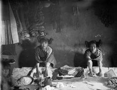 Two Native American (Hopi) women, probably of Oraibi Pueblo (Navajo County), Arizona, grind corn in square containers with metates    [between 1882 and 1900?]