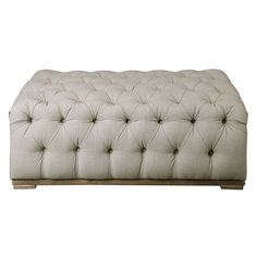 Plush ottoman features diamond button tufts in an antique white linen on an oak base, with a light gray wash.