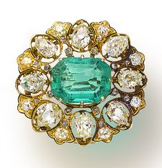 An antique emerald and diamond brooch, circa 1900 set with a cut-cornered rectangular-cut emerald, within an openwork old-cut pear-shaped diamond surround, accented by old mine and table-cut diamonds; emerald weighing approximately: 5.65 carats; estimated total diamond weight: 3.35 carats; mounted in eighteen karat gold; length: 1 1/4in.
