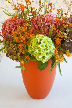 Mooi arrangement met o.a. Hortensia in groene en oranje tinten.