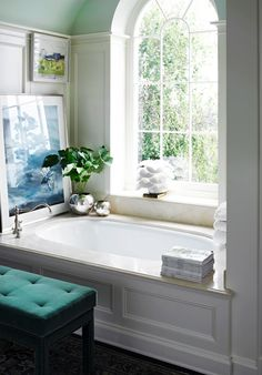 Even though I wouldn't have the window, I like this bath! I like the pretty picture at the end of the tub and the silver accent pieces, and the real plant. The hardware is elegant.