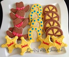Rodeo decorated sugar cookies. Royal icing. Yellow, brown, red, blue, white. Cowboy hat, wagon wheel, horse shoe, sheriff badge, star. Houston, Texas.
