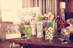 The wooden block, candy jar with scoop, and vintage-look sign on this candy station all add to the rustic ambiance. | Photography by Three Nails