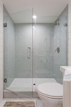 Gray herringbone pattern shower tiles in a walk-in shower enclosed with a seamless glass door. Gray herringbone pattern shower tiles in a walk-in shower enclosed with a seamless glass door. Bathroom Renos, Bathroom Renovations, Bathroom Interior, Small Bathroom, Bathroom Inspo, Bathroom Vanities, Basement Remodeling, Bathroom Ideas, Glass Tile Shower