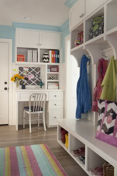 Traditional mudroom features sky blue on top part of walls and beadboard trim on bottom part of walls framing cabinets stacked over bookcase suspended over built-in desk