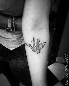 Origami crane tattoo on the left inner forearm.