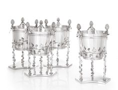 Property from the Collections of Lily & Edmond J. Safra - An unusual set of four German silver wine coolers, Johann Heinrich Stolzheise, Buckeburg, to the design of Count Ernst zu Münster, circa 1815, each formed as a bucket engraved with pales & applied with bands, supported by three ribbon-tied thyrsi entwined with grapevine, triangular bases engraved with contemporary arms, marked on edges of base plates, height 15 in.