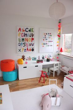 This all white playroom is filled with colourful accessories like alphabet prints and Fatboy Points. Love the garland mobile too.