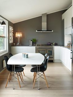 Kjøkkenet fra HTH er L-formet, med overskap på den ene veggen. Eierne valgte en rimelig benkeplate i laminat, og prioriterte heller en stor og ekslusiv gasskomfyr. Alle vegger er malt i grått, mens innredningen er hvit.=