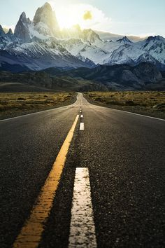 Lonely road with snow capped mountains in the distance by Jimmy McIntyre - more on www.murraymitchell.com