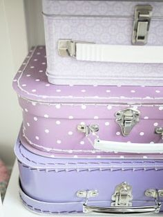 Three suitcases in lavender and orchid.