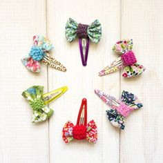 Pretty little Liberty fabric 'bow' hairclips with hand-knitted band and floral bendy clip. Available in Red, baby Pink, Purple, Sky Blue, Green and FuchsiaIdeal present or party bag filler. These pretty hairclips will make any little girl happy. Made from Liberty fabrics, with a handknitted band, the bows are then sewn securely onto a pretty floral bendy clip. Available individually or as a complete set. Comes complete on a 'Chi-Chi Moi' giftcard. Handmade in Somerset,Cotton fabric, wool…