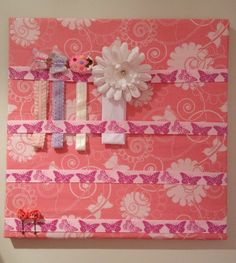 Headband and hair clip organiser Made by wrapping fabric and ribbon around a canvas and using a staple gun to secure it.