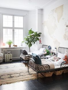 Children's room: world map wallpaper, metal bed frames, radiator for warmth, hardwood floor with rug, and plants for extra beauty.