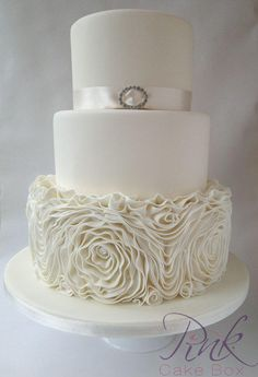 An elegant 3 tier cake in champagne with a stunning bottom tier of ruffled fondant roses finished off with a simplistic satin ribbon around the top tier adorned with a diamante brooch. This is one of the most popular designs this year so far :) I...