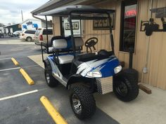 """Custom painted electric blue & silver E-Z-GO RXV Golf Cart with custom seats, 6"""" lift, 12"""" wheels & tires."""