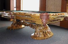 Burl accented billiard table with hand-carved body and free-form rails.