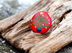 Hand Painted Beach Stone. Pretty Christmas Tree on Red Background.