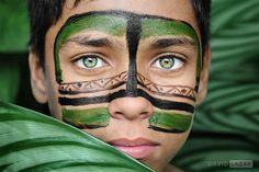 Green Eyed Boy from Brazil - Taken in Sao Paulo, a boy with face paint poses among some leaves for a portrait to feature his bright green eyes.