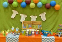 Great eye catching decor Onesie Baby Shower: decor with aqua, yellow and brown balloons yellow or aqua colored table cloth background to spice up a bland white wall and bright table cloth on table Cute!